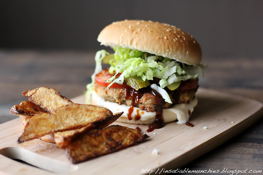The kotlet burger is filled with a kotlet, lettuce, tomato and lots of barbecue sauce, with golden potato wedges on the side.