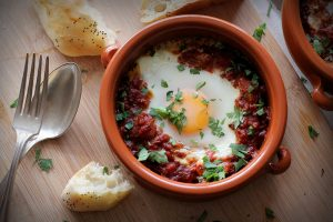 A middle eastern version of eggs and baked beans, shakshuka features a tomato-based capsicum and bean stew, served with an egg baked right into it.