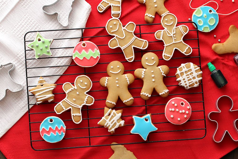 Ginger bread cookies decorated in various ways sit on a cooling rack, on red fabric