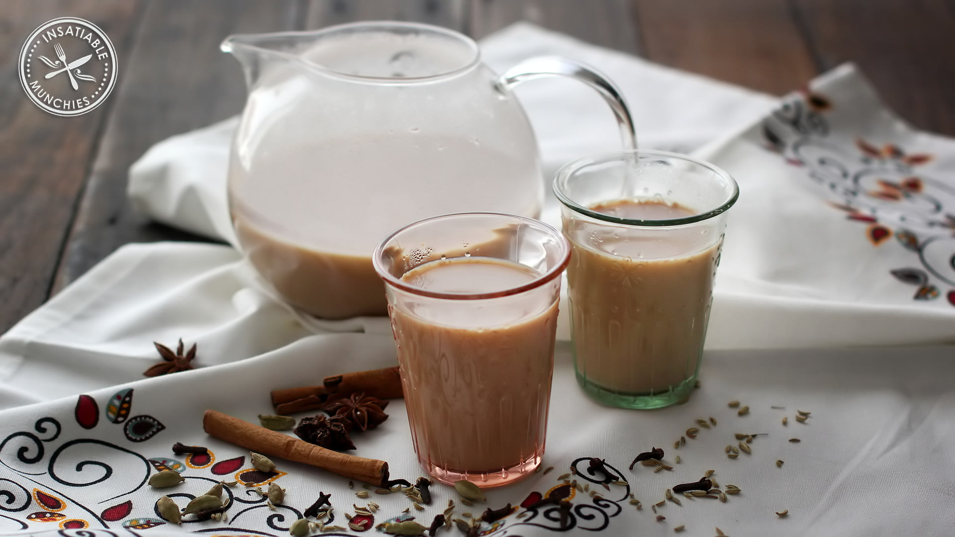 Two glasses of soy chai latte, with a glass tea pot to serve