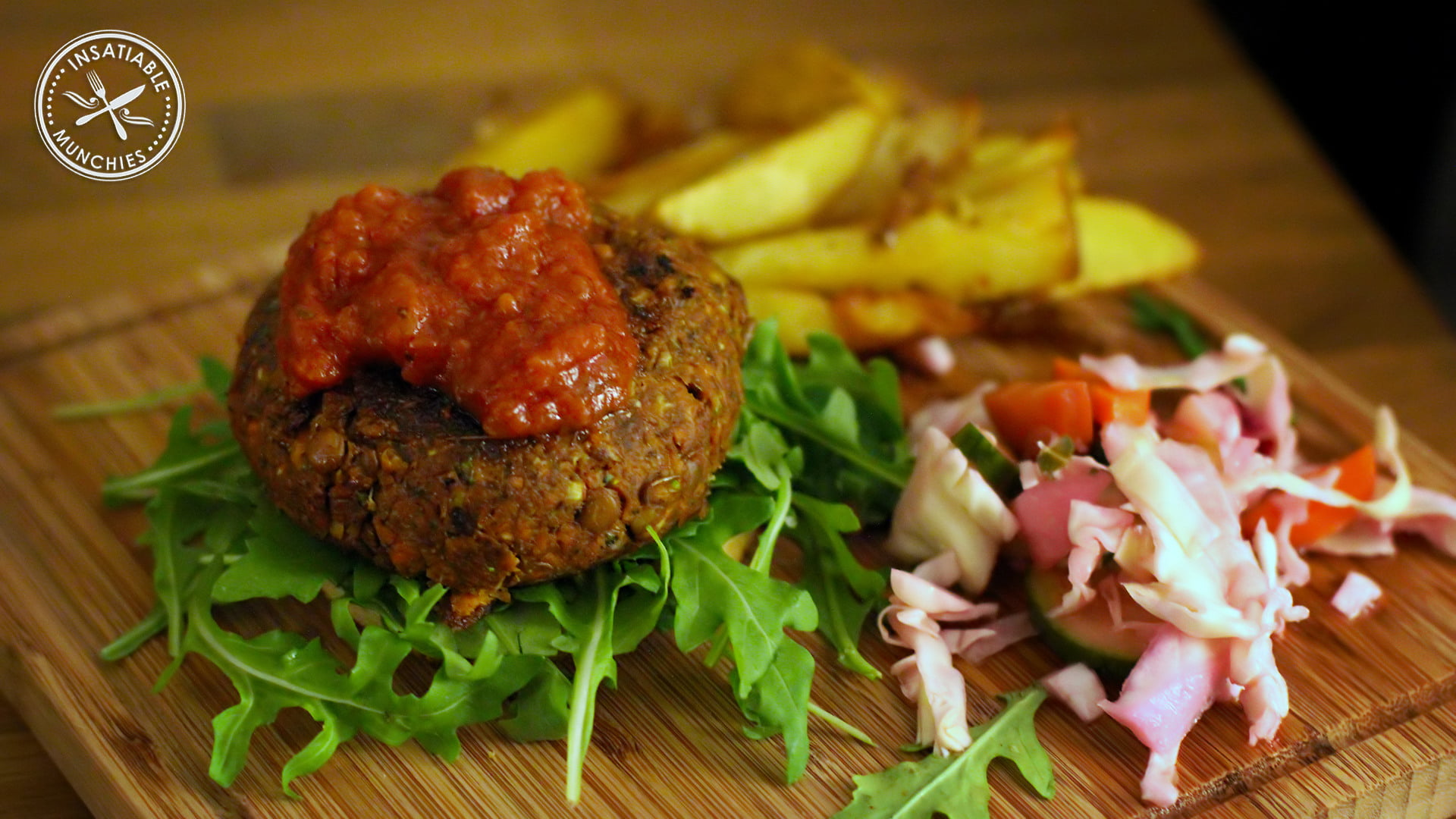 Lentil patty with a red sauce sits on fresh rocket leaves with shredded red cabbage and chips on the side.