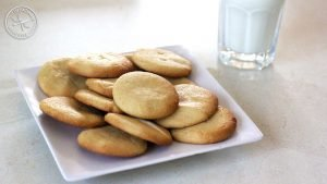A plate of cookies, with a glass of milk on the side.