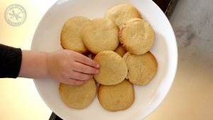 a little hand reaching for a cookie from a pile on the plate.
