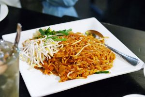 Rice stick noodles are stir fried with radish, sauce and chicken. Served with a side of chopped peanuts and fresh bean sprouts.