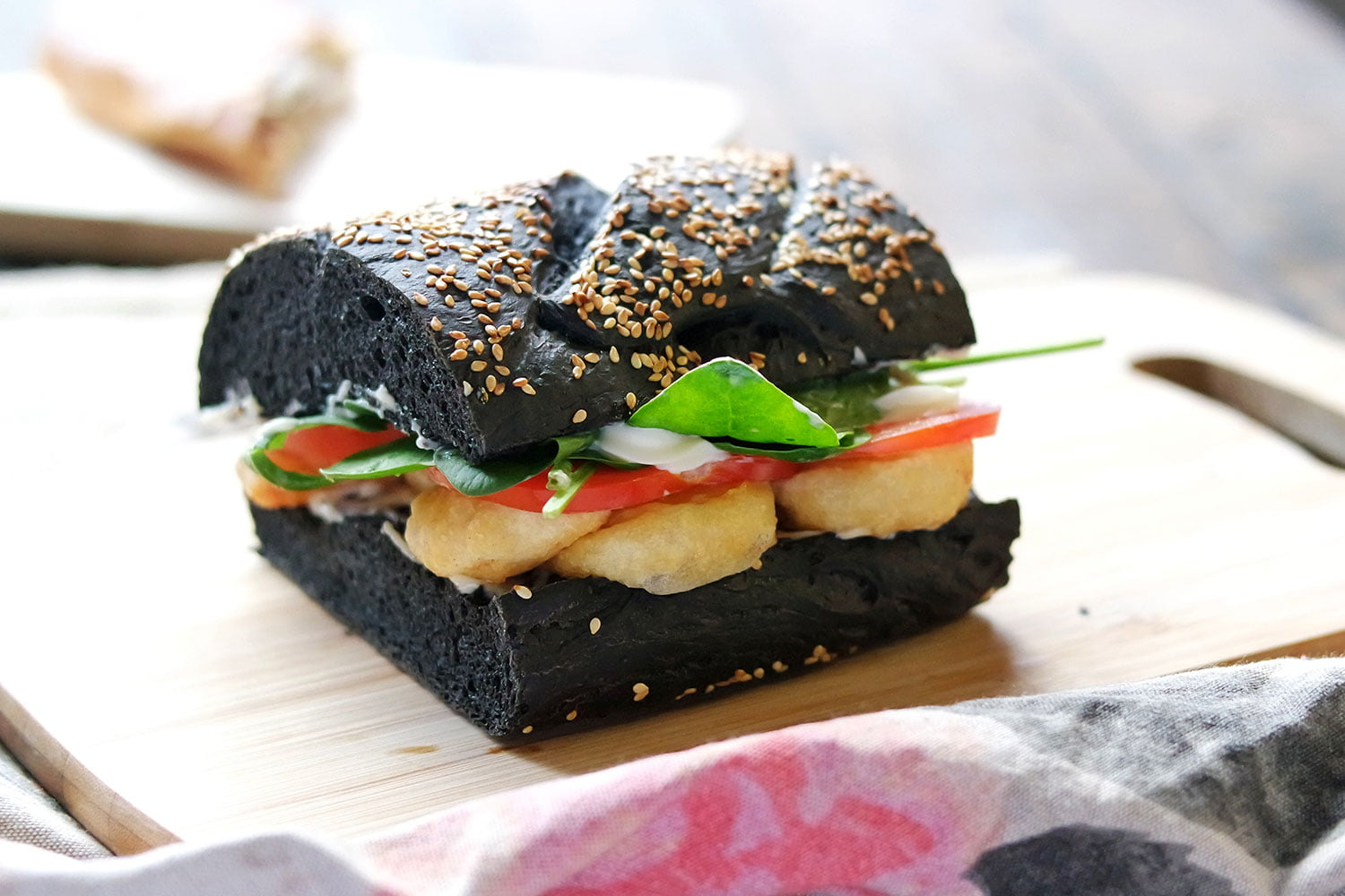 Shrimp sandwich made with battered shrimp, kewpie mayo, tomato, lettuce, on black squid ink bread.