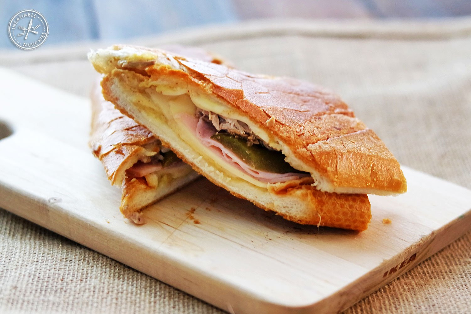 A cuban sandwich - mustard, swiss cheese, pickles ham, braised pork shoulder - is halved and sits on a wooden board.