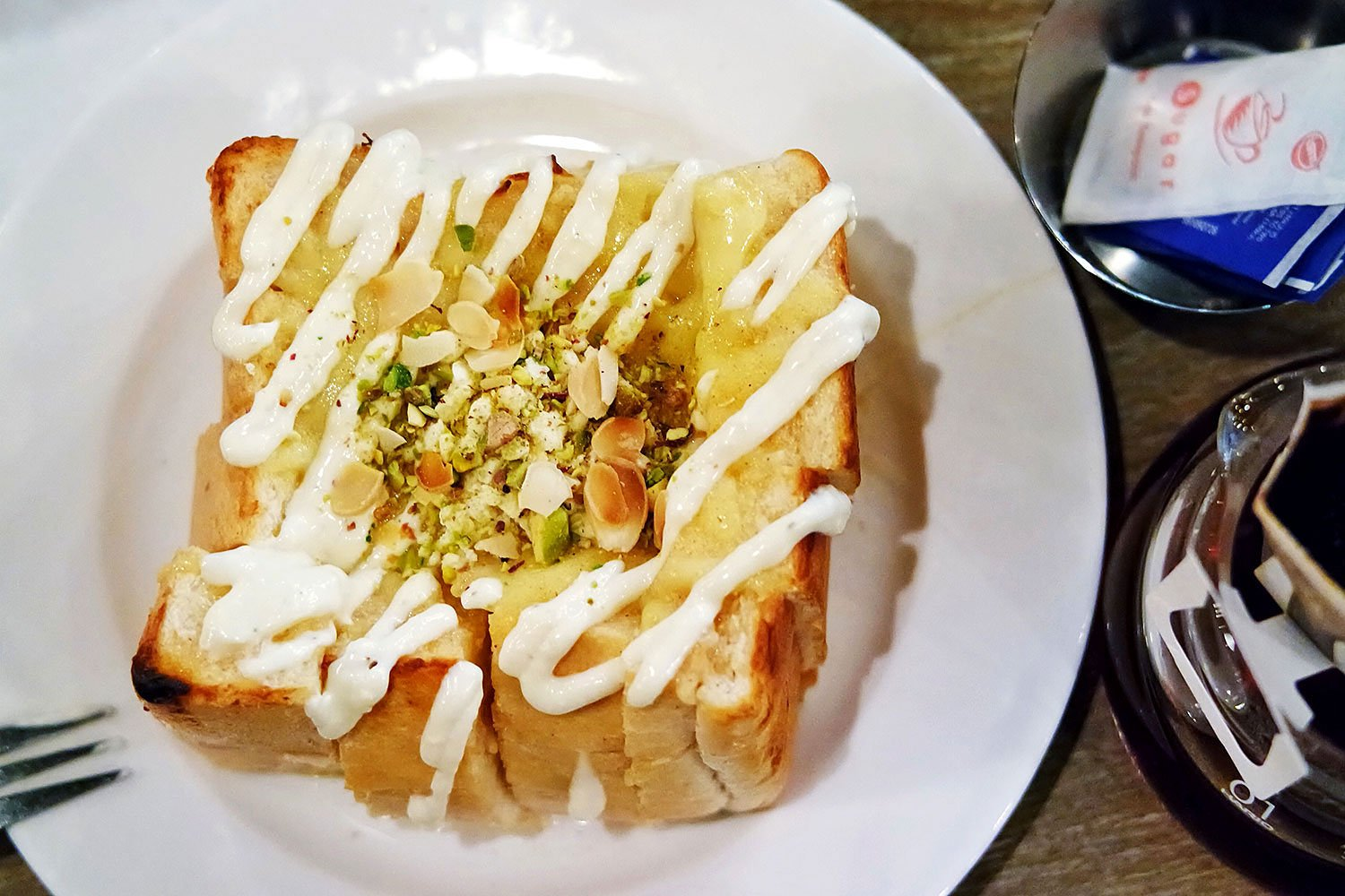 A thick slab of white fluffy bread is toasted, and covered in honey, melted cheese, and garlic cream.