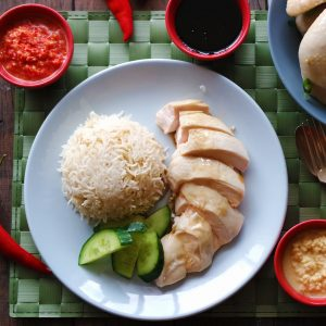 A plate of fragrant rice cooked in chicken stock, garlic and ginger is served with delicately poached chicken that's cut into thick slices. Cuts of cucumber garnish the blue plate.
