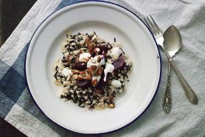 A salad of black rice and pearl cous cous, served with a roasted garlic and tahini dressing, greek yoghurt, baby beetroot and smoked almonds. Here, it's served on a blue-rimmed tin plate and laid next to a fork and spoon, on a blue tea towel.