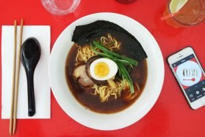 """A bowl of """"the darkness"""" ramen from Rising sun workshop, photographed aerially with cutlery and a mobile phone flanking it from either side."""