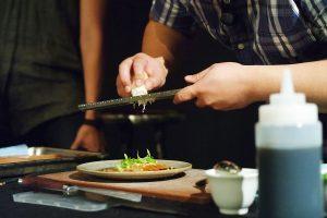 Chef Brendan Fong grates horseradish over a place of soy cured hiramasa kingfish