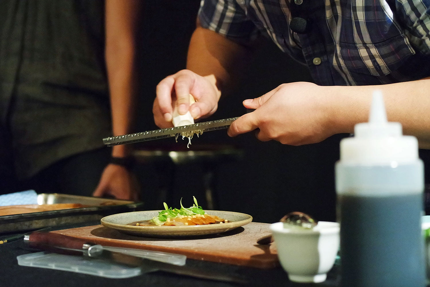 Chef Brendan Fong grates horseradish over a place of soy cured hiramasa kingfish