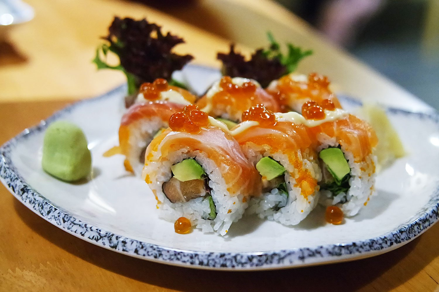 6 pieces of inside out sushi roll, filled with salmon, avocado and lettuce leaves, topped with salmon and salmon roe.