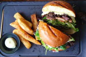A Korean BBQ Burger with chips and garlic mayo served on a black slate at Miel Burger in Brisbane