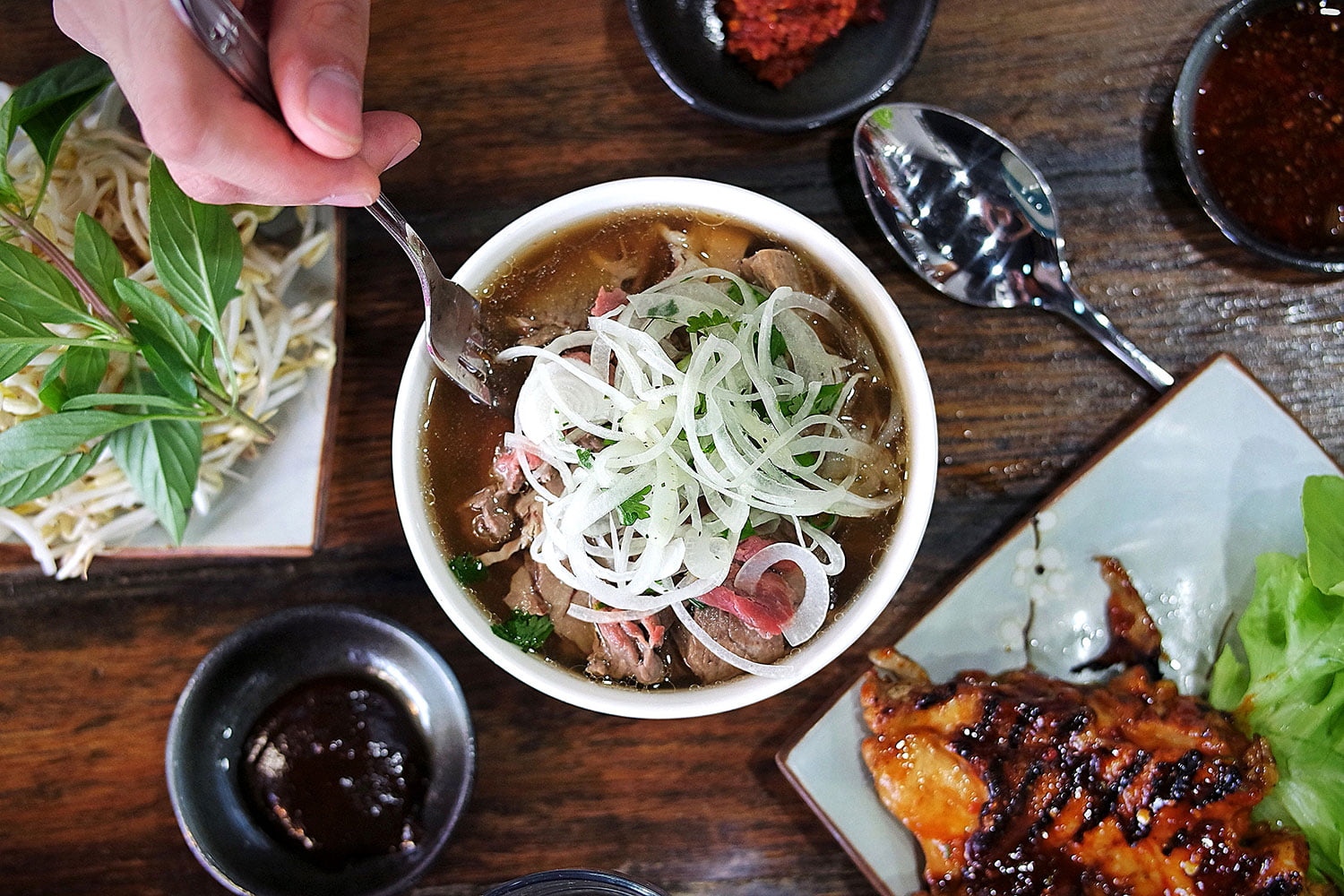 A fork digging into a bowl of pho amongst a table of food that includes grilled chicken