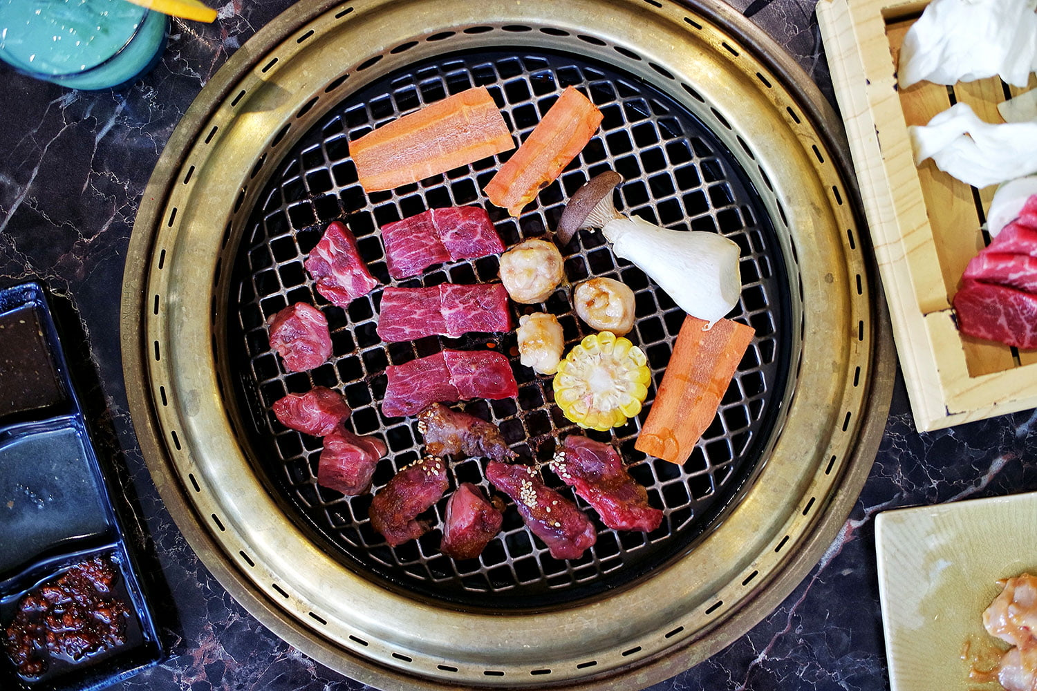 Aerial shot of the barbecue filled with wagyu beef pieces and vegetables