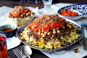 A plate of Koshari sits on a table set with smaller plates, cutlery, and middle easter inspired napkins