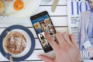 a phone on the table with the instagram screen up, surrounded by coffee and breakfast