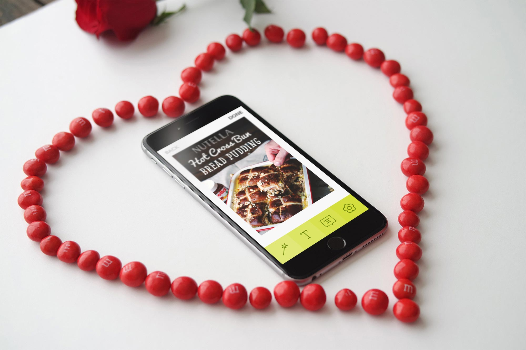 An iphone 6+ sitting in a heart made with red M&Ms, with the Little Moments App displayed on the screen.
