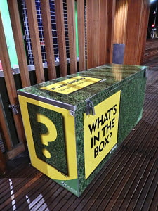 A large mystery box with question marks on the side
