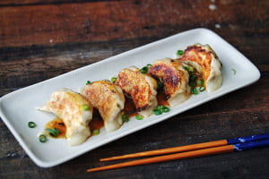 Shiitake Mushroom Gyozas, lined up on a long plate and garnished with a miso dipping sauce and finely chopped green spring onions